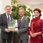 Ed Nijpels (links) neemt de VHG-handleiding Het Levende Gebouw in ontvangst uit handen van VHG-directeur Egbert Roozen en conceptontwikkelaar Kim van der Leest.